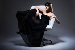 Genuss. Noble blonde Entspannung der eleganten Frau im Stuhl. Schwarzes Kleid und Maske mit Federn Lizenzfreie Stockfotografie
