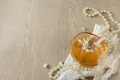 Eleganz-Parfümflasche mit weißen Perlen Stockfotos