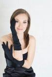 Eleganzfrau in den schwarzen Handschuhen und Kleid auf hellem baclground Lizenzfreie Stockfotografie