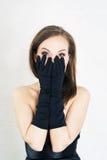 Eleganzfrau in den schwarzen Handschuhen und Kleid auf hellem baclground furcht Stockfotografie