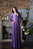 Eleganzfrau im langen violetten Kleid Luxus, indoo Stockbilder