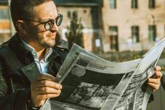 Eleganzschönheitsmann in den Gläsern las Zeitung Stockfoto