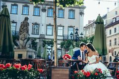 Elegent newlywed couple is holding hands and touching heads while sitting at the otdoor wooden table. Beautiful nature. Background Stock Image