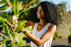 Elegent smiling african girl with green eye shadows using the green plastic trigger spray for outdoor plants. Elegent smiling african girl with green eye stock photos