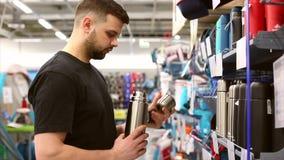 Elegir un termo en la tienda Comprador masculino en la alameda que elige el termo para acampar Escena en la alameda metrajes