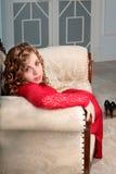 Elegnt mooie jonge vrouw die in rode kleding in klassiek binnenland in camera kijken Stock Foto's