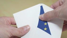 Eleição na União Europeia - pondo um voto da bandeira da UE dentro do envelope vídeos de arquivo