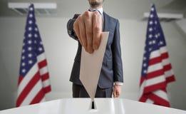 Eleição ou referendo no Estados Unidos O eleitor guarda a cédula acima disponivel do envelope Bandeiras dos EUA no fundo Imagem de Stock Royalty Free