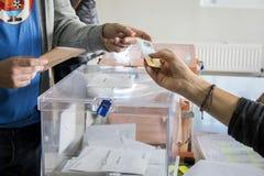Eleitor que mostra seu carteira de identidade ao lado das urnas eleitorais no dia de eleição geral espanhol no Madri, Espanha imagem de stock royalty free