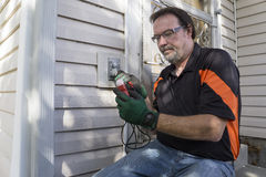 Elektricien Checking Outside Outlet voor Klant Stock Afbeelding