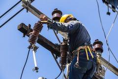 Elektricien die aan de elektriciteitspool werken Stock Fotografie