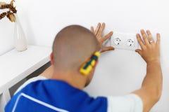 Elektricien die de Contactdoos van de Muur installeert Arbeider Stock Afbeeldingen