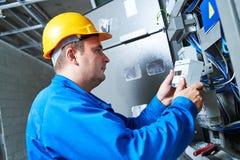 Elektricien die energie installeert - besparingsmeter stock afbeelding