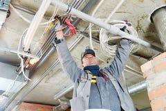 Elektricien die met aanleg van kabelnetten werken Stock Fotografie
