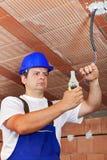 Elektricien die met bedrading in een nieuw gebouw werken Stock Afbeeldingen