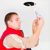 Elektricien die met draden en andere werktuigen werken Stock Foto's