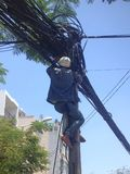 Elektricien die polen beklimmen, die machtslijnen herstellen vietnam Stock Afbeelding