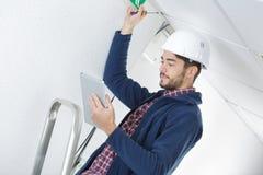 Elektricien die zich op ladder bevinden en tablet gebruiken royalty-vrije stock fotografie