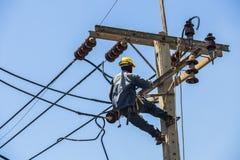 Elektricien het hangen op de elektriciteitspool stock foto's