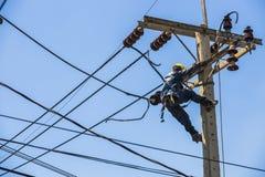Elektricien het hangen op de elektriciteitspool Stock Foto
