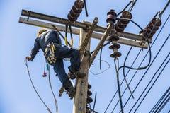 Elektricien het hangen op de elektriciteitspool royalty-vrije stock afbeeldingen