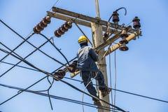 Elektricien het hangen op de elektriciteitspool Stock Afbeeldingen