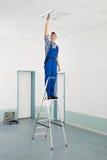 Elektricien Installing Ceiling Light royalty-vrije stock foto's