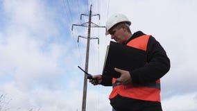 Elektricien met documentatie dichtbij hoogspanningslijn stock videobeelden