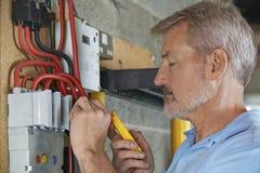 Elektricien Testing Power Supply in Fuseboard royalty-vrije stock afbeelding