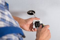 Elektricienhanden die muurcontactdoos installeren Stock Foto