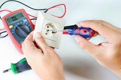 Elektricienhanden met contactdoos elektriciteit en mensenconcept Digitale multimeter schroevedraaier royalty-vrije stock fotografie