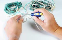 Elektricienhanden met contactdoos elektriciteit en mensenconcept Digitale multimeter schroevedraaier stock fotografie