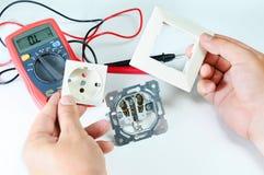 Elektricienhanden met contactdoos elektriciteit en mensenconcept Digitale multimeter schroevedraaier stock afbeeldingen