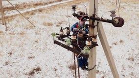 Elektricienhersteller die aan toren bij de elektrische post werken stock videobeelden