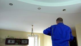 Elektricienkerel die of een lichte lamp van de halogeenvlek installeren vervangen in plafond stock videobeelden