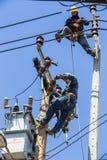 Elektriciens die aan de elektriciteitspool werken stock fotografie