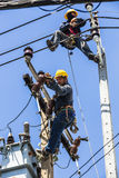 Elektriciens die aan de elektriciteitspool werken royalty-vrije stock afbeelding