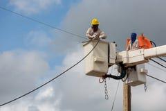 elektriciens die draad van de machtslijn herstellen op stroom royalty-vrije stock foto