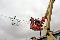 Elektriciens die Kerstmislichten plaatsen op stadsstraat royalty-vrije stock afbeeldingen