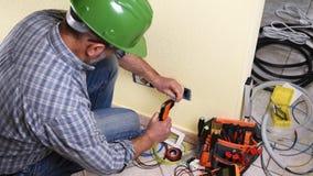 Elektricientechnicus aan het werk aangaande een woon elektrisch systeem Bouwnijverheid stock footage