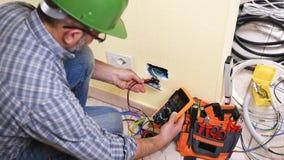 Elektricientechnicus aan het werk aangaande een woon elektrisch systeem Bouwnijverheid stock videobeelden