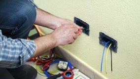 Elektricientechnicus aan het werk aangaande een woon elektrisch systeem Bouwnijverheid stock video