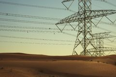 Elektriciteit of hoogspanningsmachtslijnen in dessert bij zonsondergang royalty-vrije stock foto
