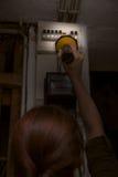 Elektriciteitspanne, elektriciteitsbesnoeiing, vrouw met flitslicht die br controleren Royalty-vrije Stock Fotografie