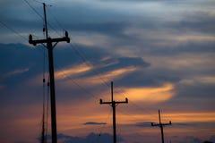 Elektriciteitspolen op kleurrijke hemel, zonsondergang Stock Afbeelding