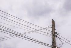 Elektriciteitspool en straatlantaarn ingewikkelde bedrading met Donker S Stock Foto's