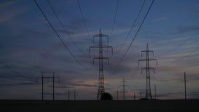 Elektriciteitspylonen en de avondhemel stock foto's