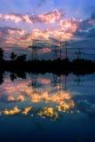 Elektriciteitspylonen en lijnen bij schemer bij zonsondergang Stock Foto