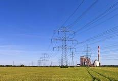 Elektriciteitspylonen met macht een post in het midden van een landbouwgebied Stock Afbeelding
