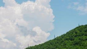 Elektriciteitspylonen op een rij op de achtergrond van mooie bewolkte hemel timelapse stock videobeelden